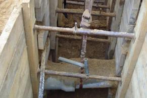 Sichern einer vorhandenen Rohrleitung im Holzbohlenverbau